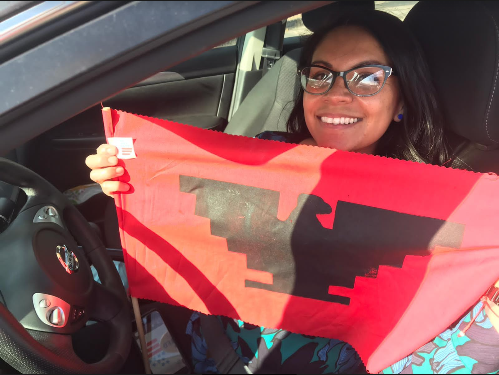 Driver sits behind the wheel smiling and holding up a red and black United Farm Worker flag emblazoned with a black aztec eagle on a red field.