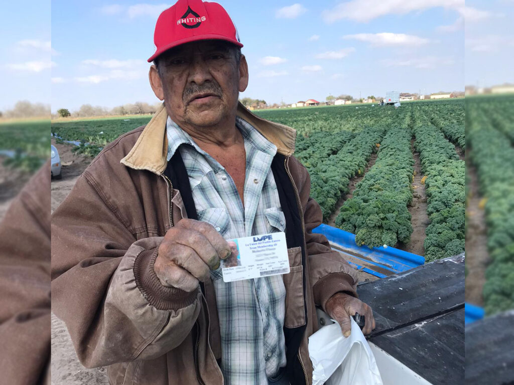 Farmworker with red cap and heavy work jacket poses in front of field furrows holding up a LUPE membership card in one hand and a bag of PPE in the other